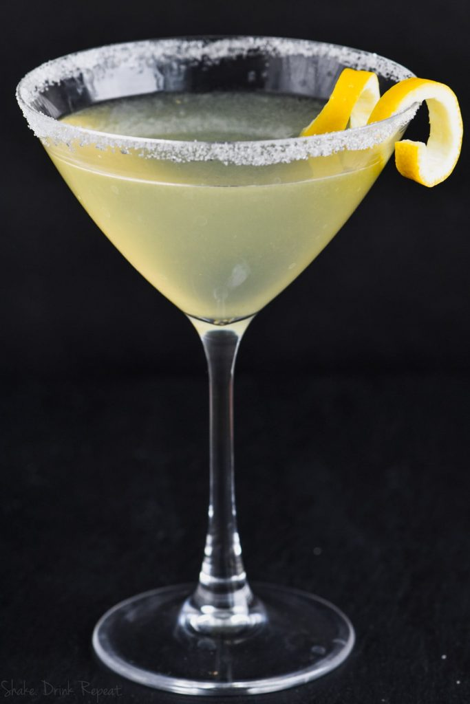 front view of martini glass rimed with sugar and lemon curl and filled with lemon drop martini