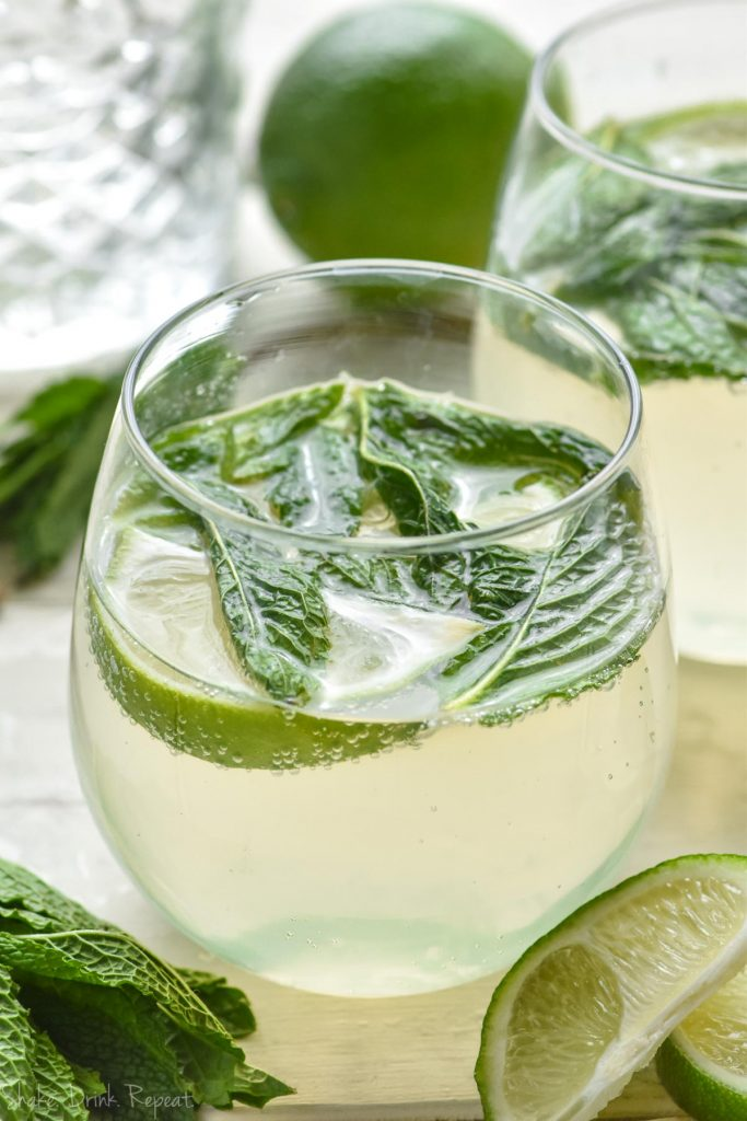 glass of mojito sangria cocktail with mint and limes