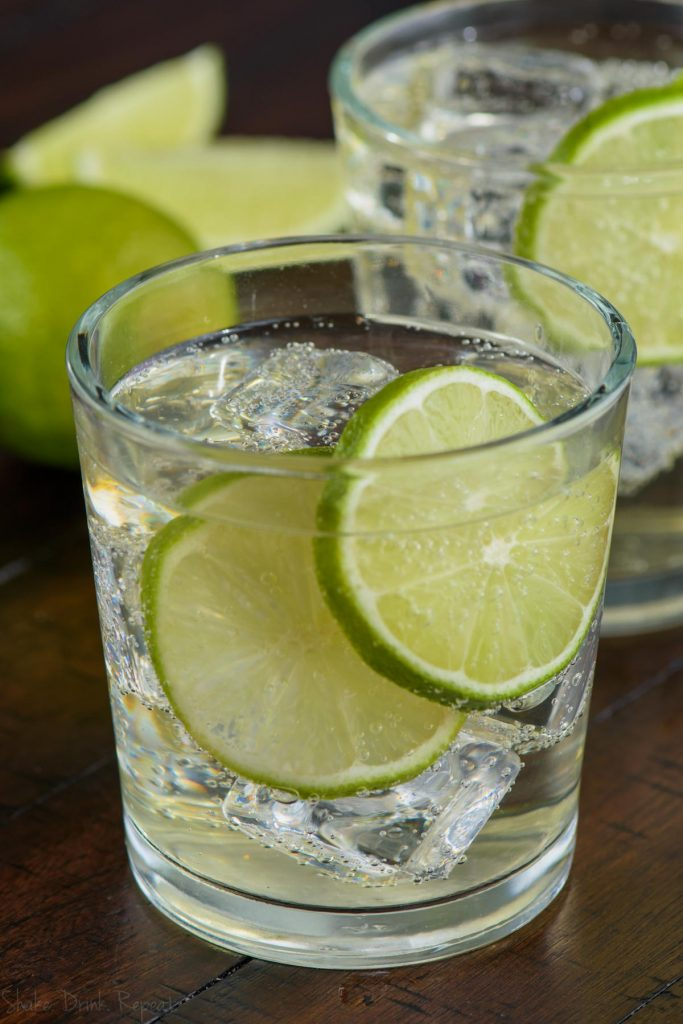 glass of the perfect gin and tonic with two lime slices