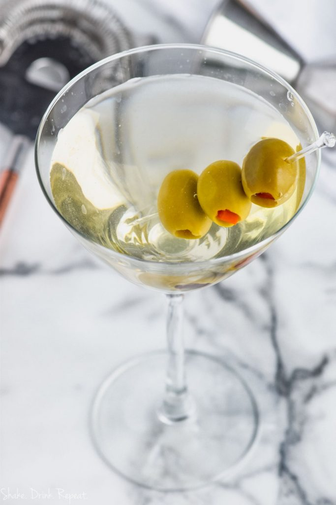 overhead view of dirty martini recipe with three olives