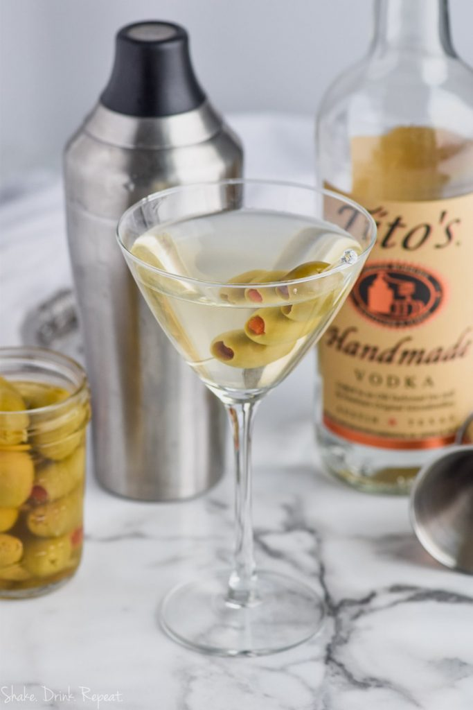 dirty martini recipe with three olives, martini shaker, and bottle of titos