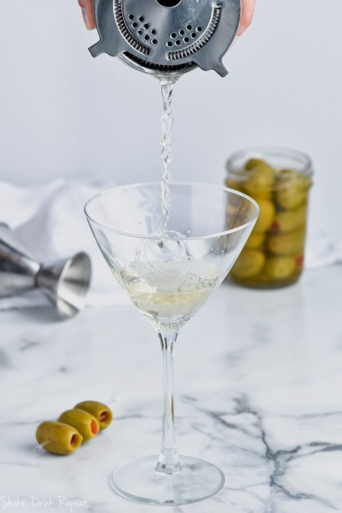 dirty martini recipe being strained into a martini glass