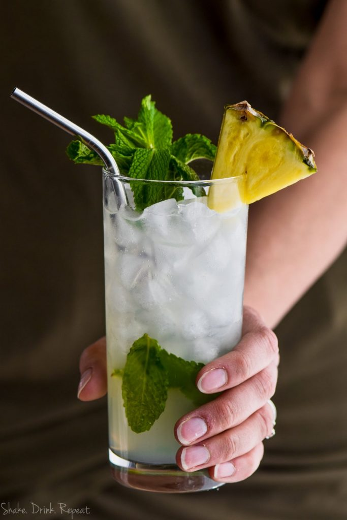 hand holding a pineapple mojito garnished with mint and fresh pineapple