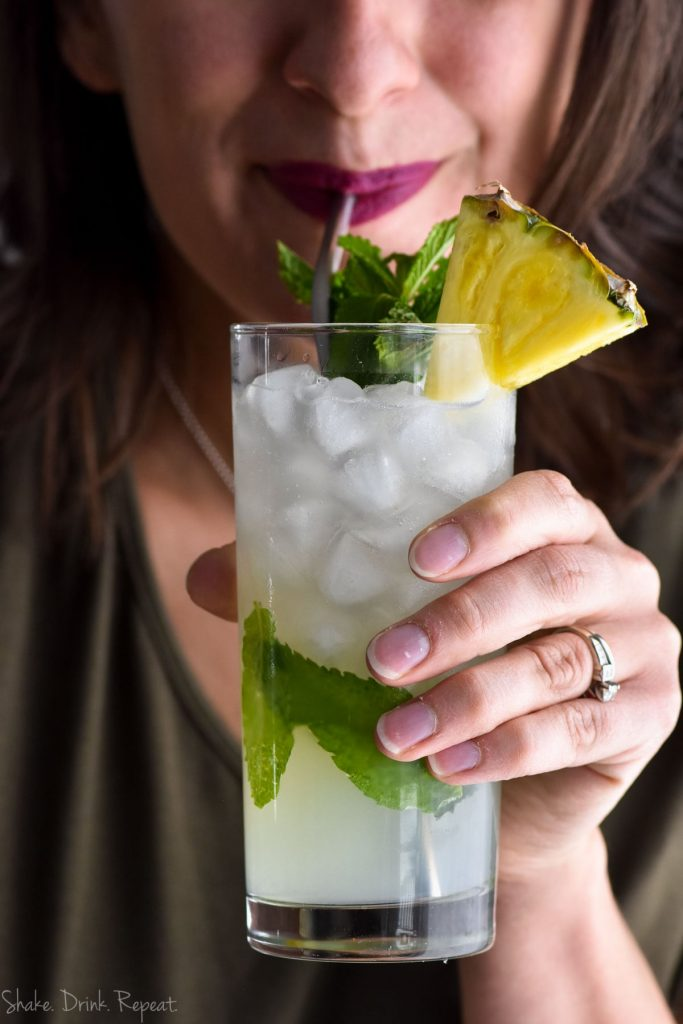 woman sipping pineapple mojito through a metal straw