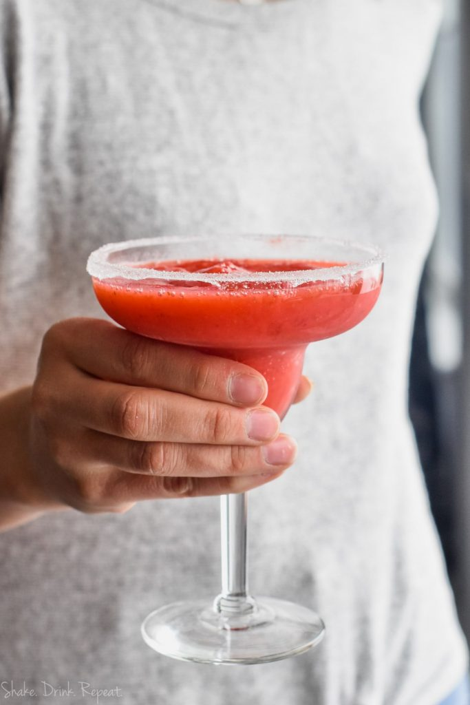 woman holding a frozen strawberry margrita