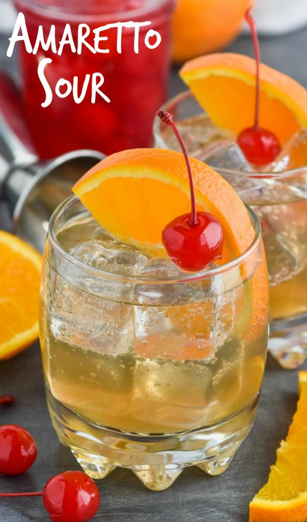 an amaretto sour in a glass with a cherry and an orange