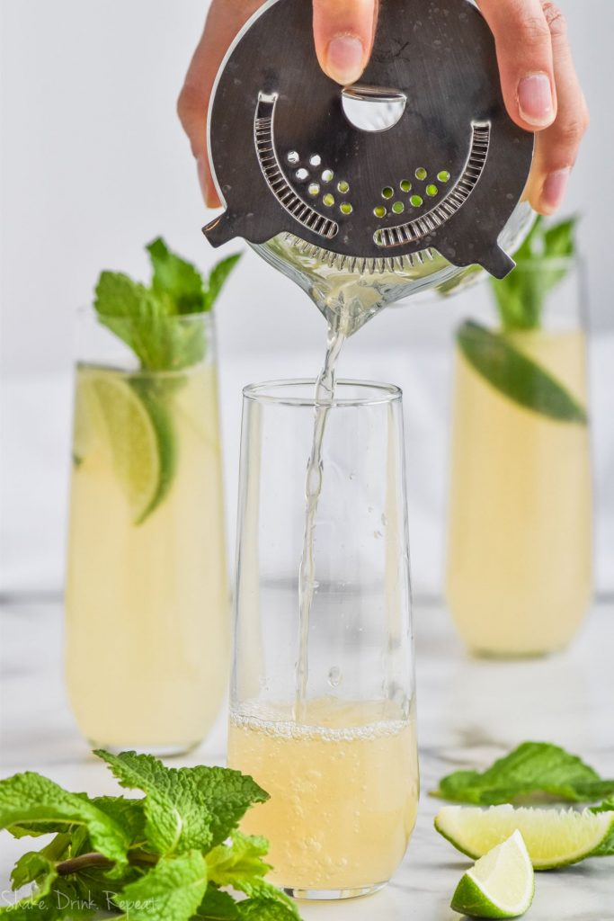 moscow mule being strained into a champagne glass