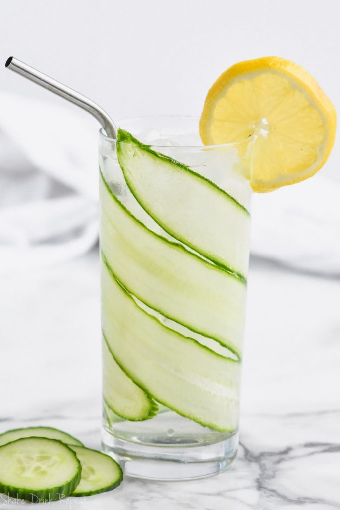 cucumber lemon gin and tonic in tall glass lined with sliced cucumber