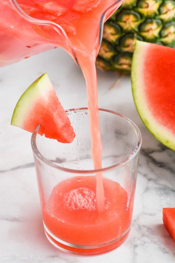pouring watermelon rum punch into a glass