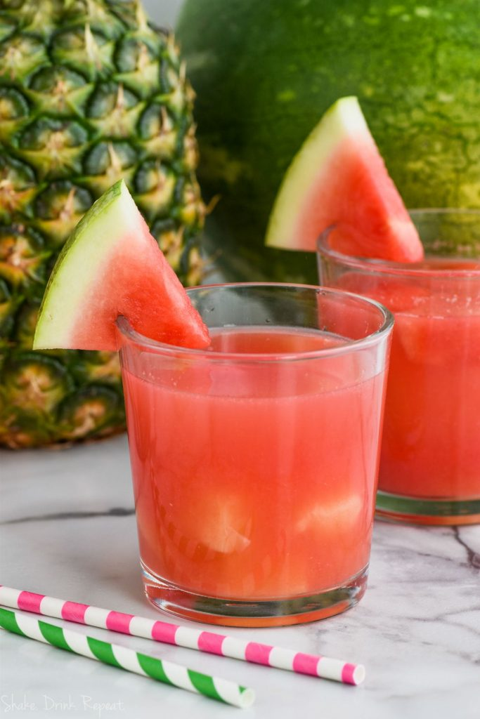 cup of rum punch recipe with floating pineapple and watermelon