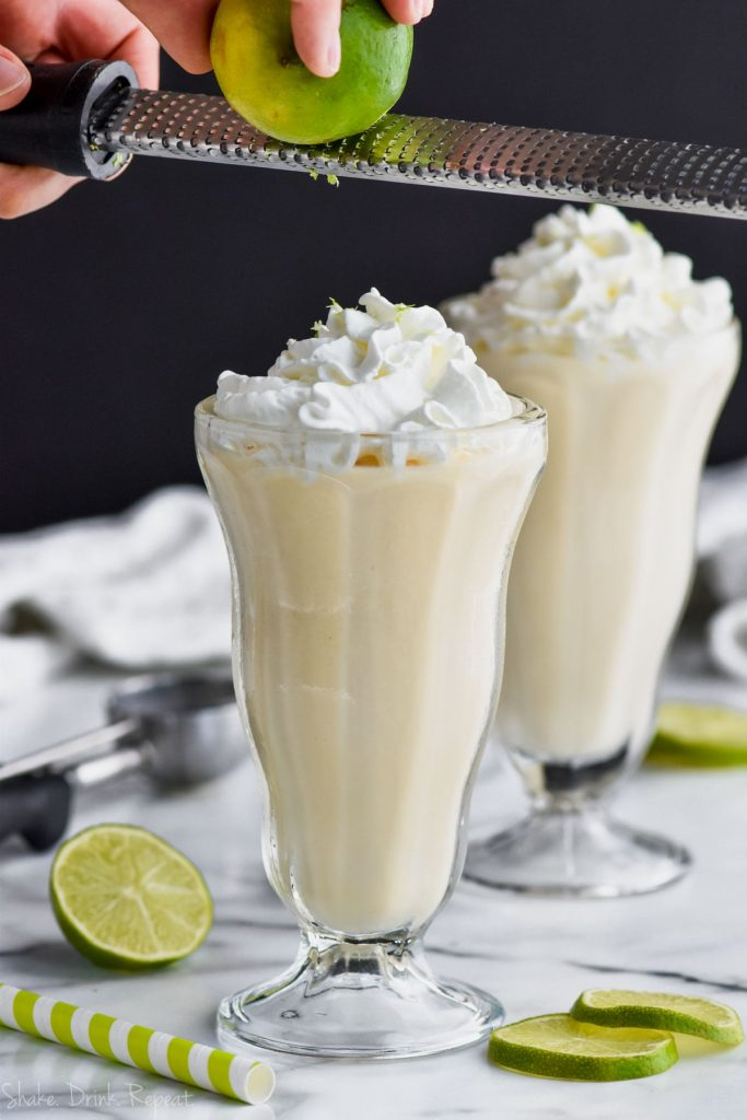 zesting a lime onto whipped cream on a margarita milkshake