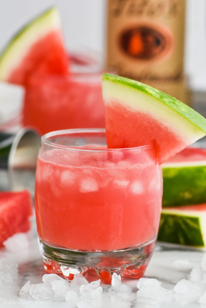 glass of watermelon vodka tonic garnished with a watermelon wedge