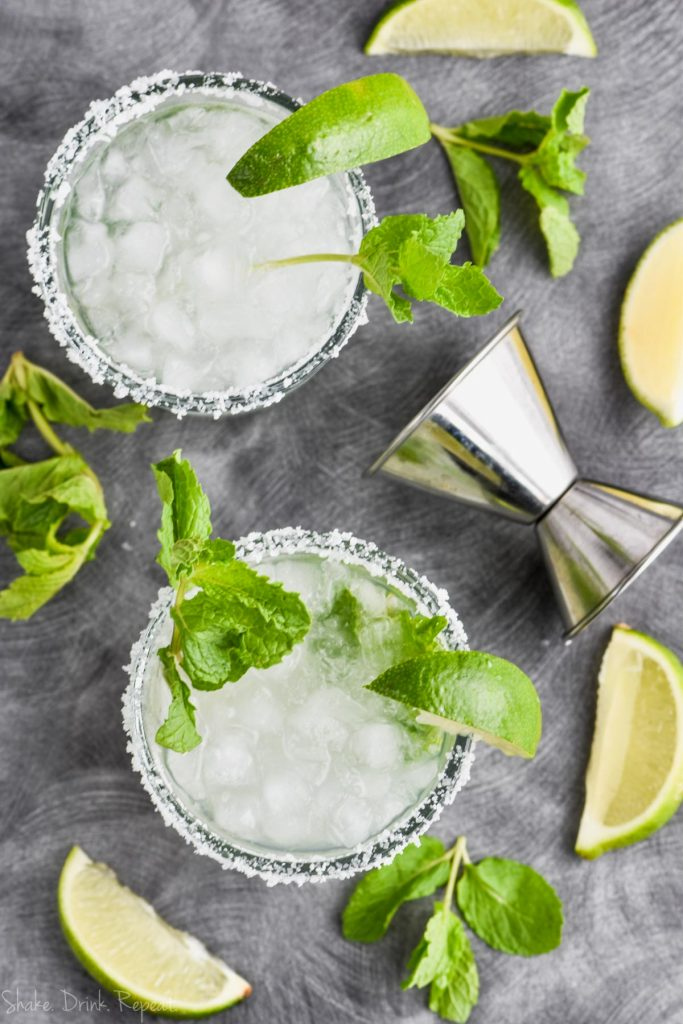 overhead view of two mojito margaritas in salt rimmed glasses with mint and lime wedges