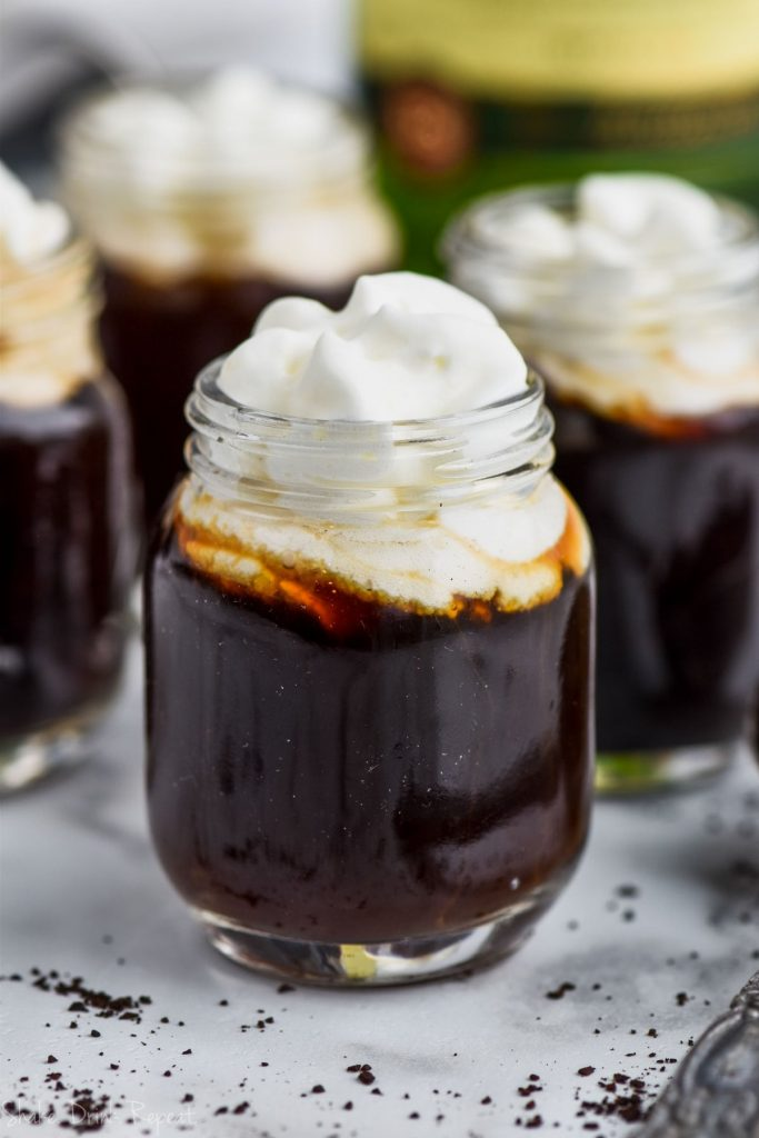 close up of irish coffee shot topped with whipped cream