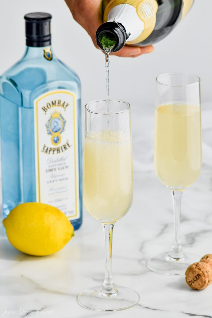 champagne being poured into a glass of french 75