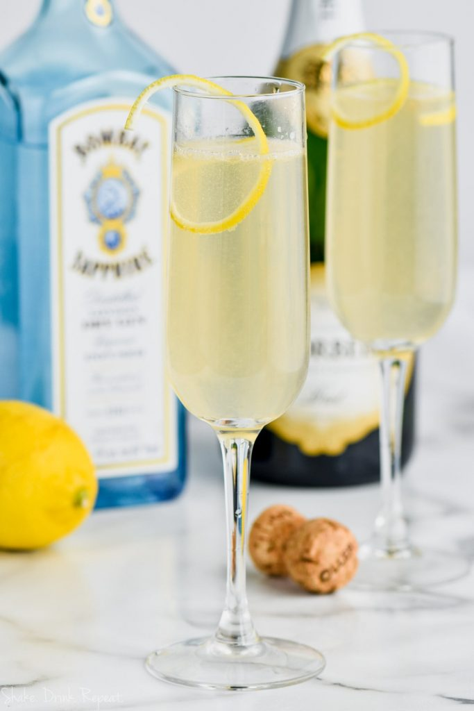 two champagne glasses of french 75 with the ingredients