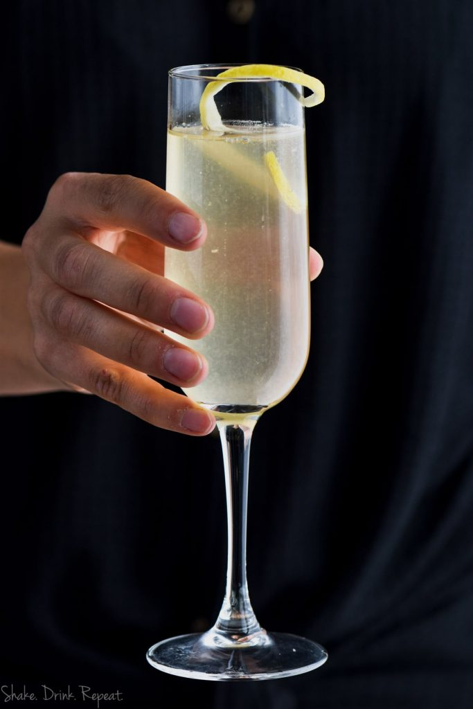 woman holding a champagne glass of french 75 with gin