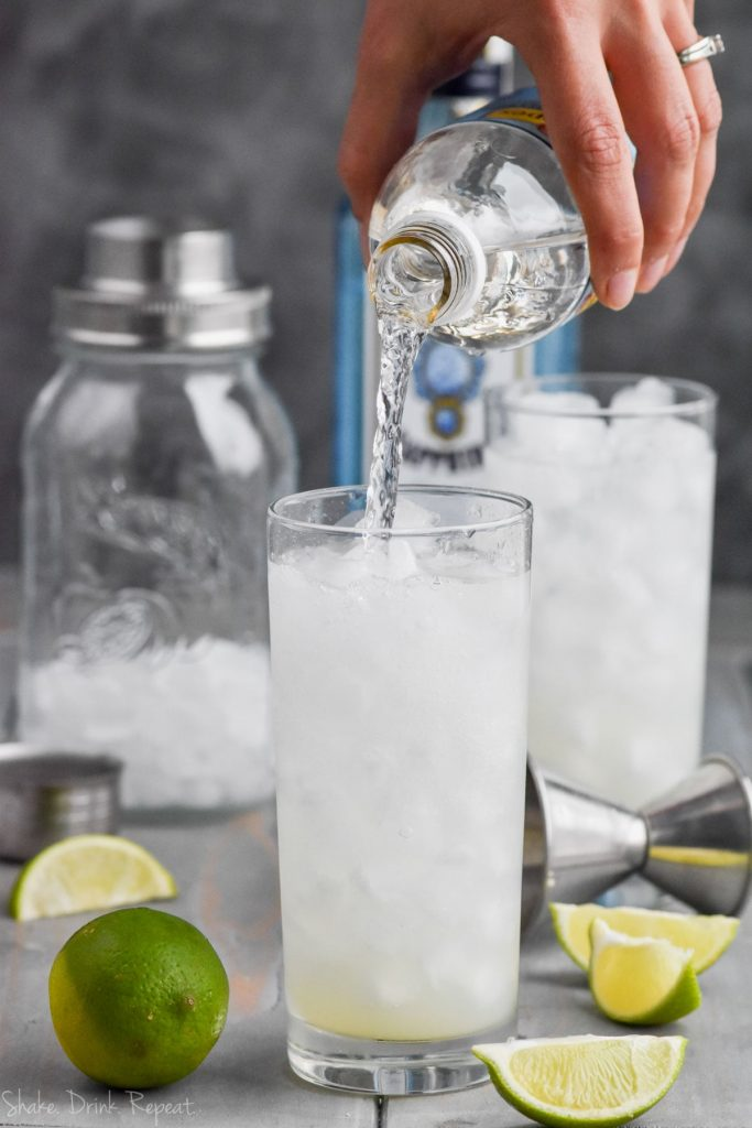 pouring club soda into a glass of gin rickey drink