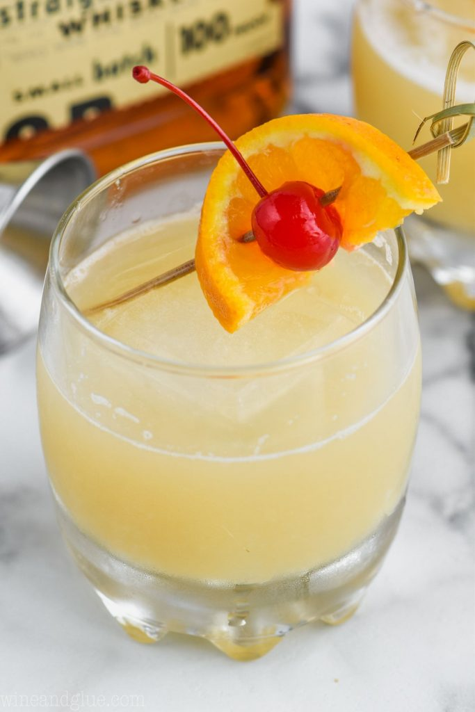 the best whiskey sour recipe garnished with an orange and cherry