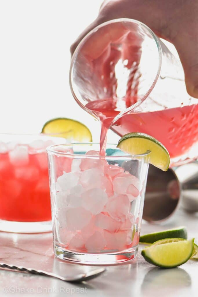 Picture of Sea Breeze being poured into a glass from a pitcher. Drink in a glass garnished with limes