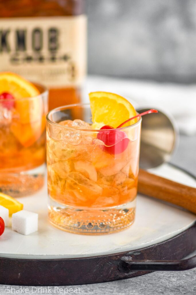 Two glasses of old fashioned with ice, cherry, orange slice and muddler sitting off to the side
