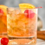 Glass of old fashioned with ice, cherry and orange on a tray with cherry and muddler