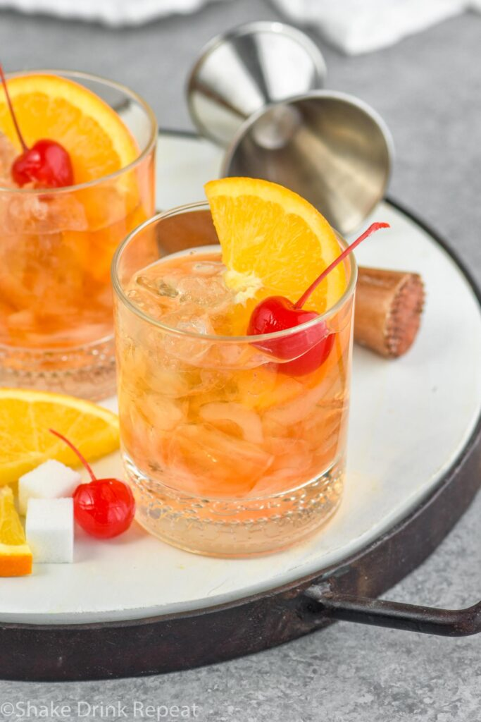 Two glasses of old fashioned with ice, cherry, orange slice and muddler sitting off to the side with a sugar cube