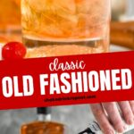 Two glasses of old fashioned with ice, cherry, orange slice and muddler sitting off to the side with a cherry