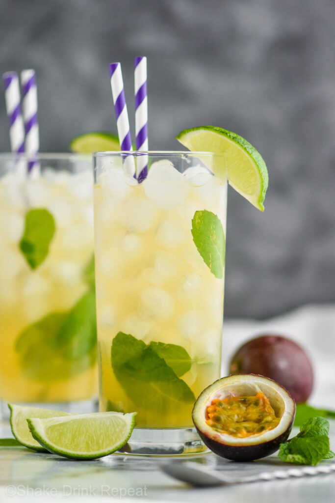 Two glasses of Passion Fruit Mojito with ice, straws, limes, mint and fresh fruit.