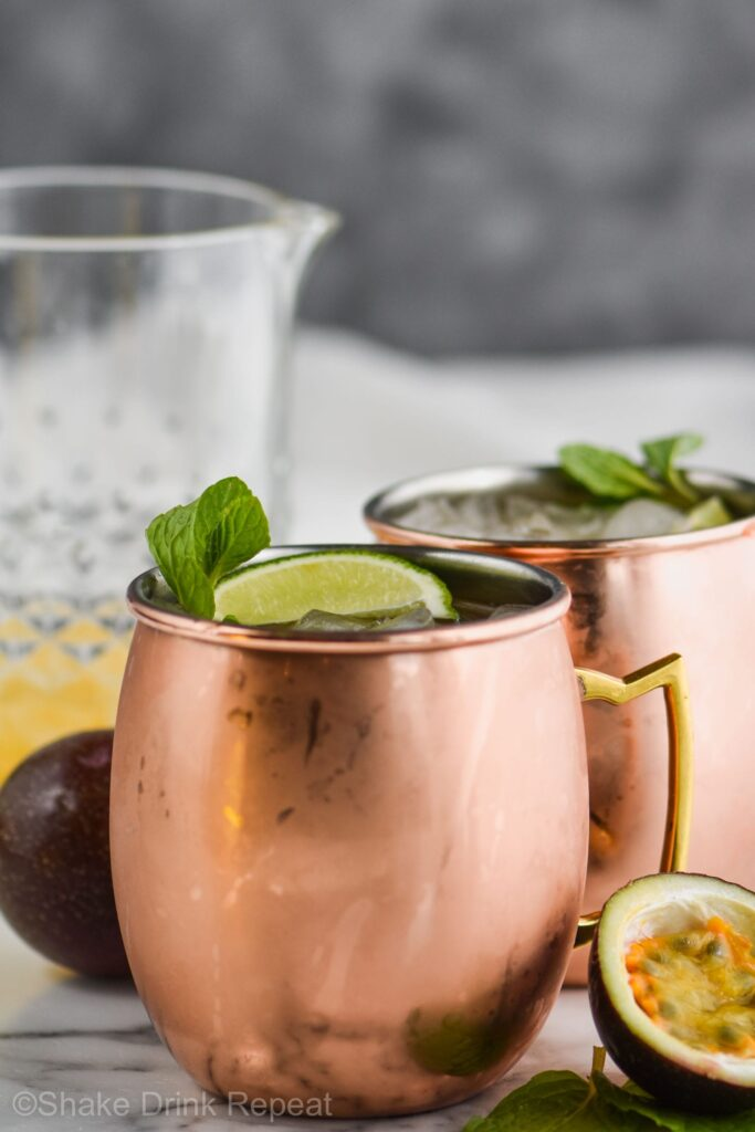 two copper mugs of passion fruit moscow mules with ice, limes, and fresh mint leaves