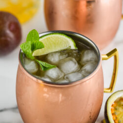 two copper mugs of passion fruit moscow mule with ice, lime and fresh mint leaves