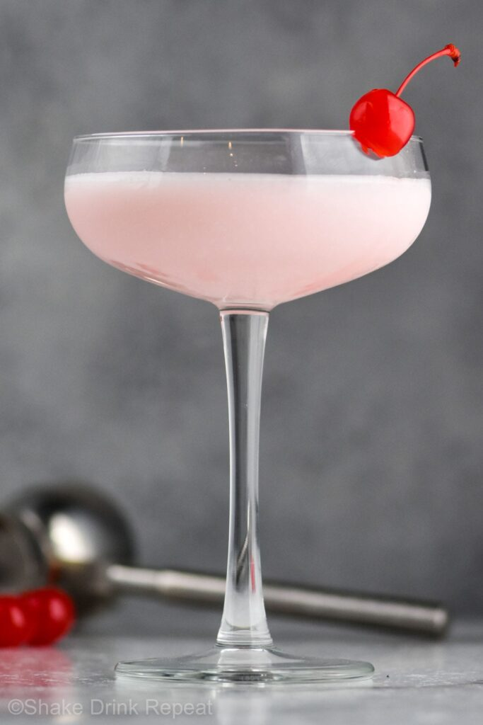 Pink lady drink in a glass with a cherry