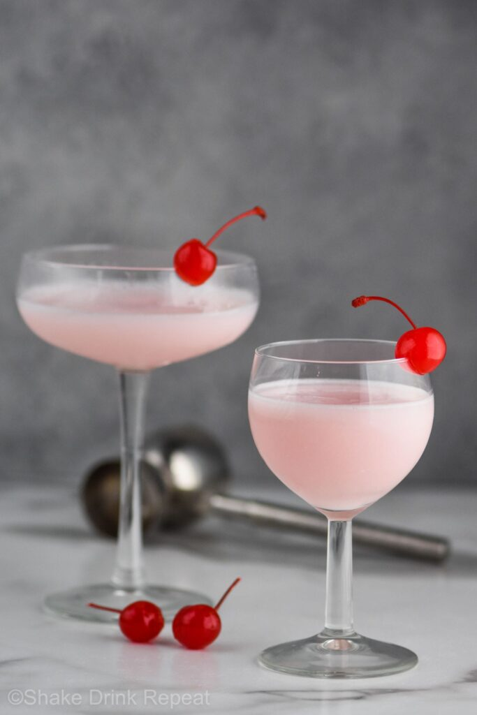 Two pick lady drink in glasses with cherries in the glasses and in the picture
