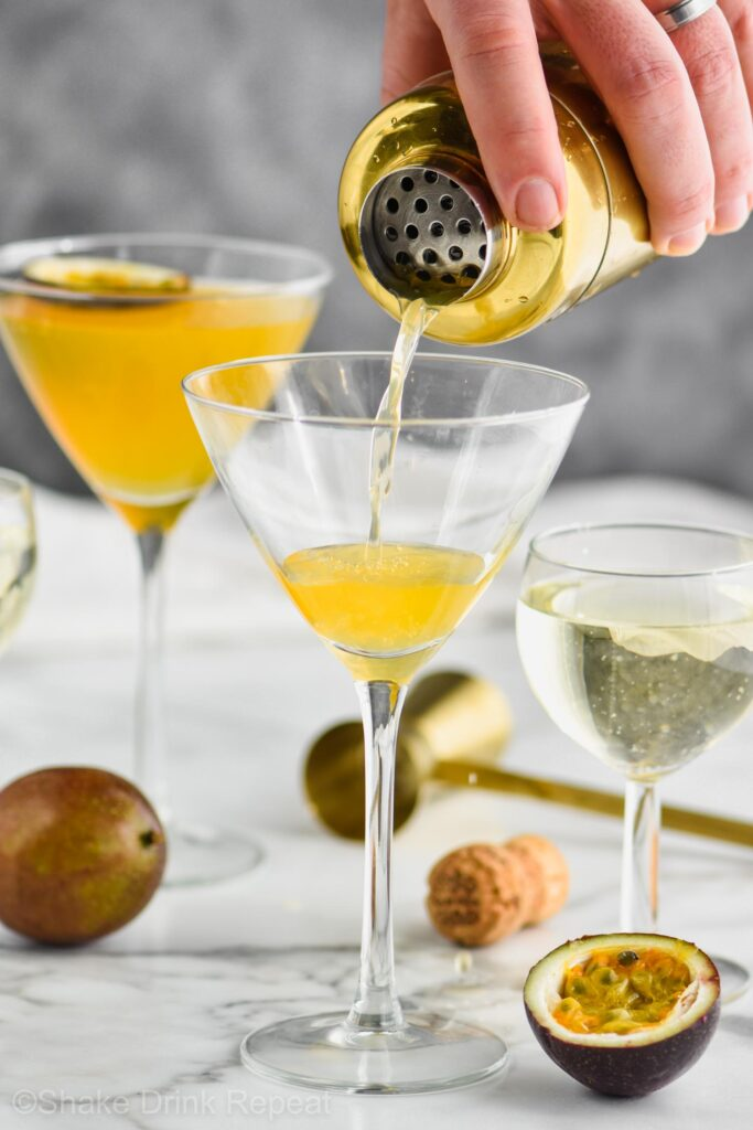 Glass with drink being poured into it with passion fruit garnishment around it