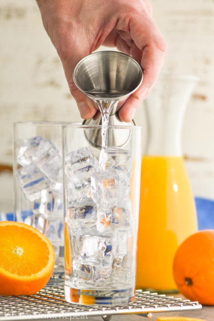 Glass filled with ice being filled with vodka, garnished with an orange