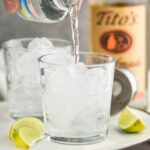 Two glasses of Vodka Soda with lime wedges and bottle of Tito's on the sides, bottle of club soda being poured