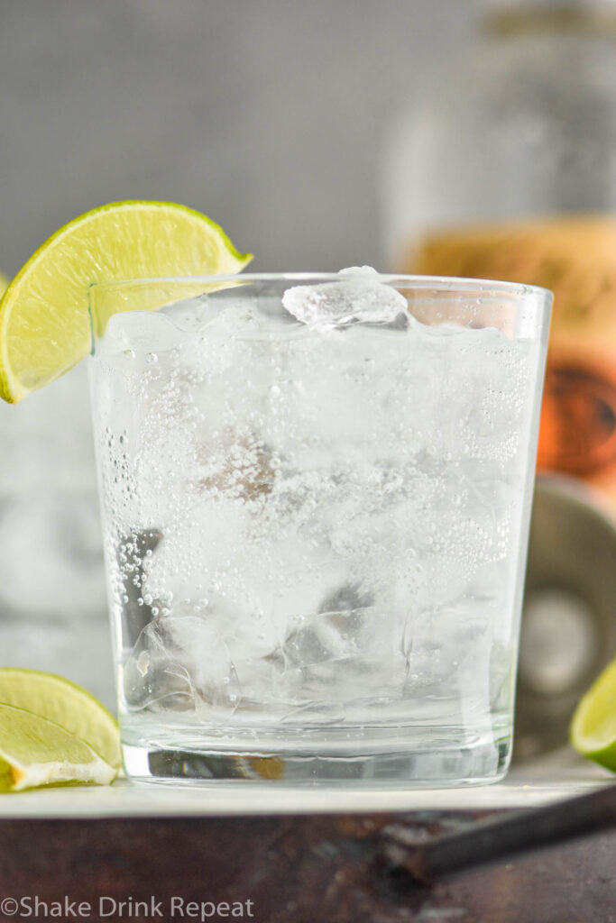 Glass of Vodka Soda with ice and lime wedges