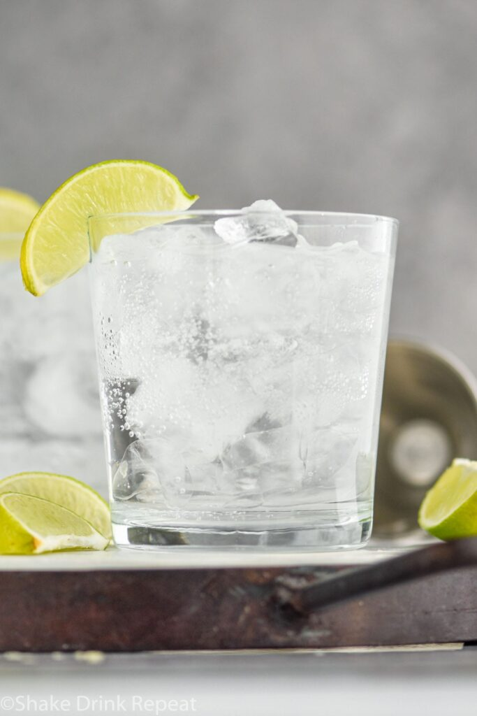 A glass of Vodka Soda with ice and lime wedges