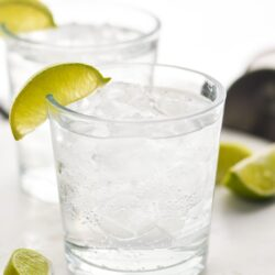 Two glasses of Vodka Soda with ice and lime wedges