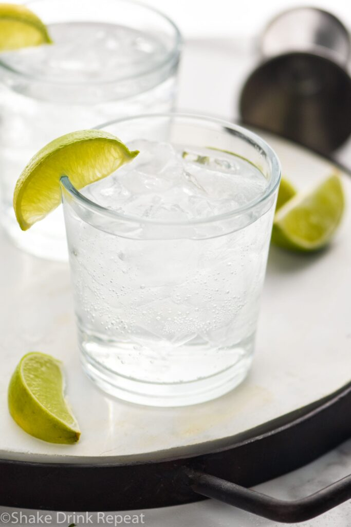 Two glasses of Vodka Soda with lime wedges and jigger off to the side