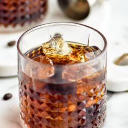 Two glasses of Black Russian with ice, surrounded by coffee beans and a jigger off to the side