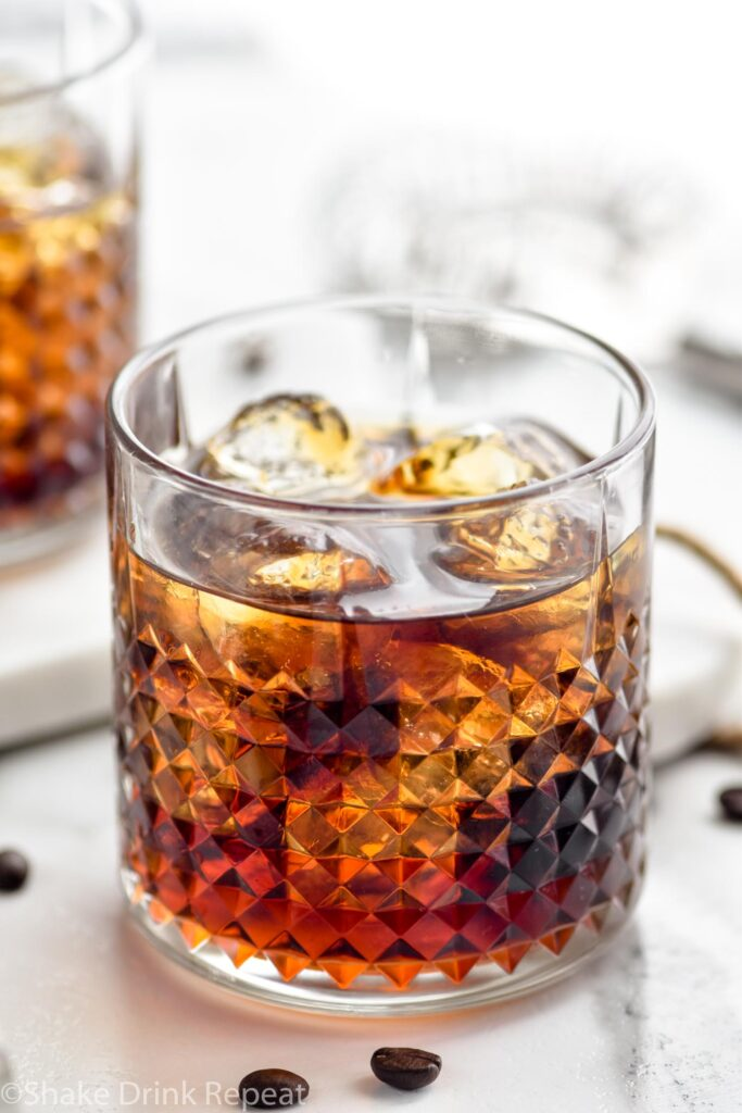 Two glasses of Black Russian with ice, surrounded by coffee beans and a strainer off to the side