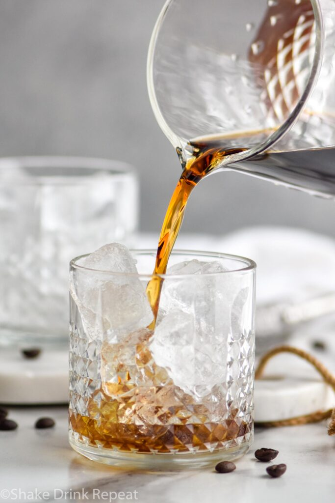 Pouring Black Russian into a glass with ice surrounded by coffee beans
