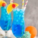 two glasses of Blue Lagoon cocktail recipe wtih orange slice garnish and cherry