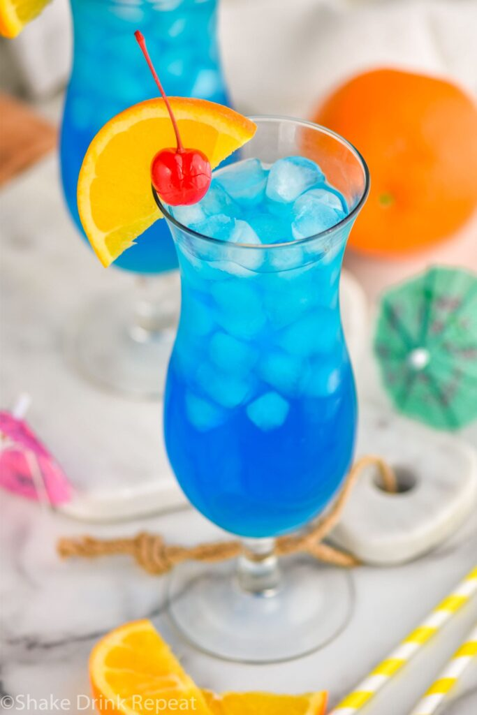 glass of blue lagoon cocktail with orange slice and cherry garnish