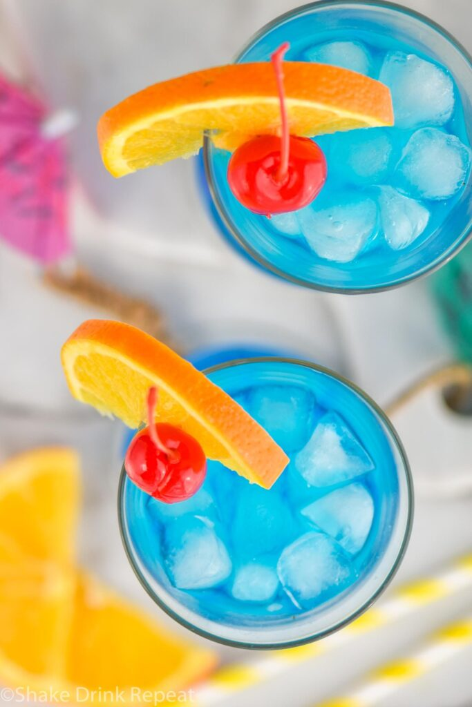 two glasses of blue lagoon cocktail with ice, orange slice and cherry garnish
