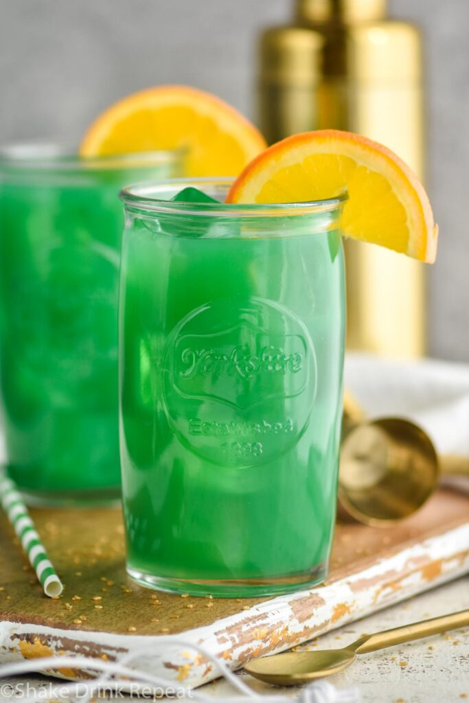 Two glasses of Drunk Leprechaun with orange garnish, spoon and straw on the side