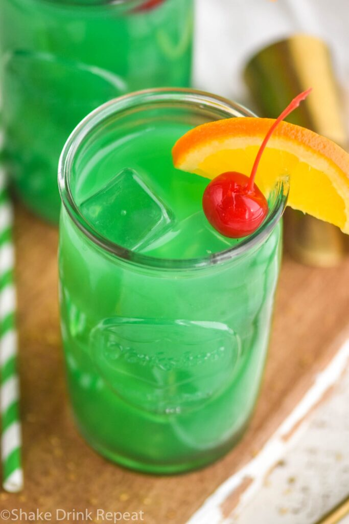 Two glasses of Drunk Leprechaun with orange and cherry garnish, spoon and straw on the side