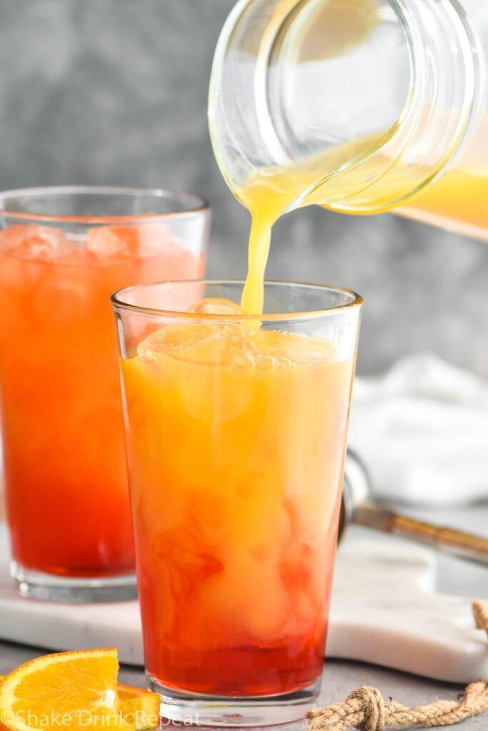 two glasses of garibaldi cocktail with ice and orange juice