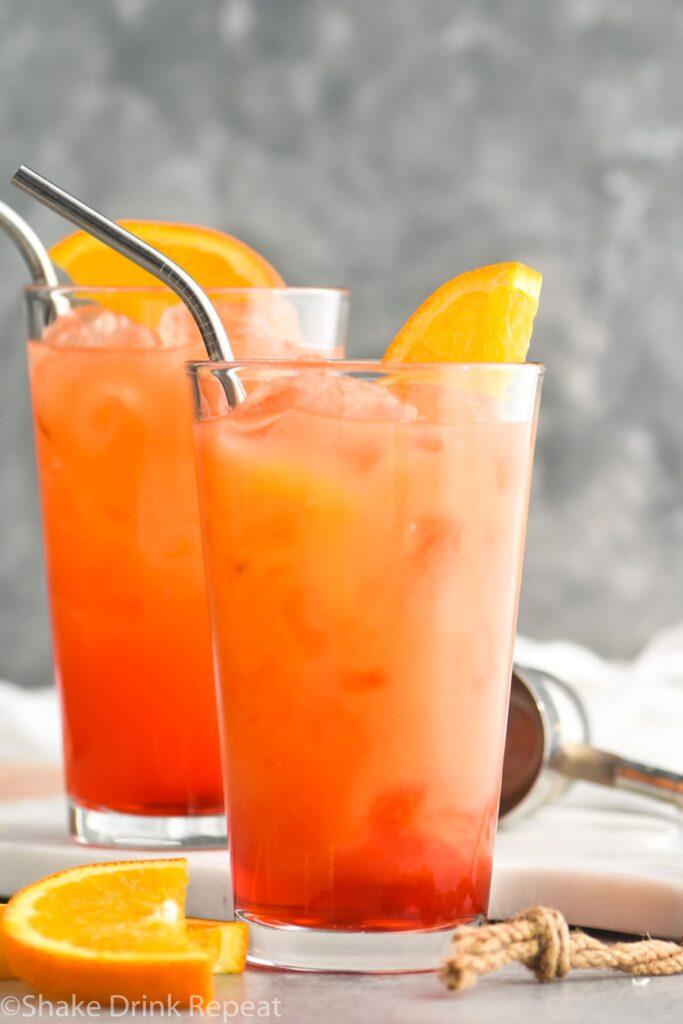 two glasses of garibaldi with ice, straws, and orange garnish